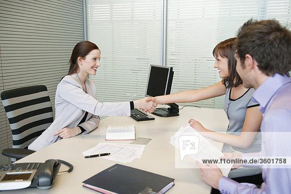 Weibliche Immobilienmaklerin schüttelt sich die Hand mit einem Paar