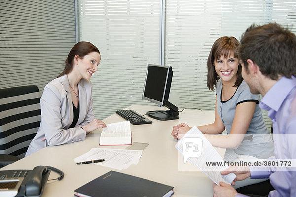 Immobilienmaklerin und ein Ehepaar diskutieren in einem Büro