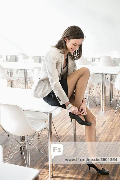 Geschäftsfrau beim Anpassen ihrer Sandale
