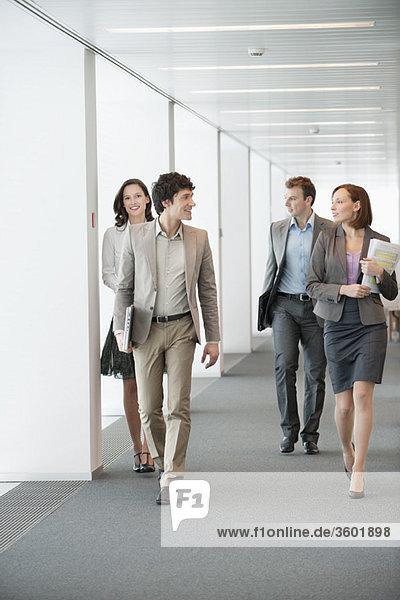 Geschäftsleute  die im Flur eines Büros spazieren gehen