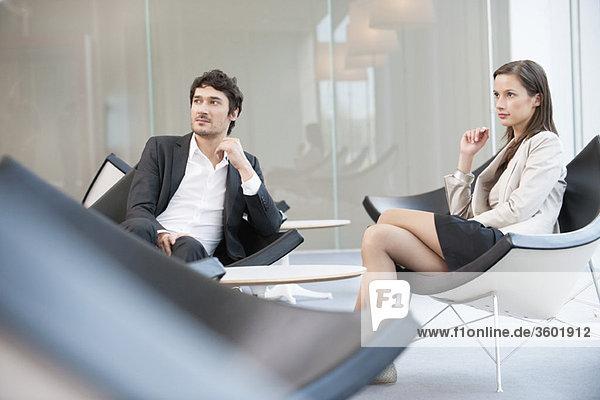 Geschäftsleute sitzen auf Stühlen im Wartezimmer