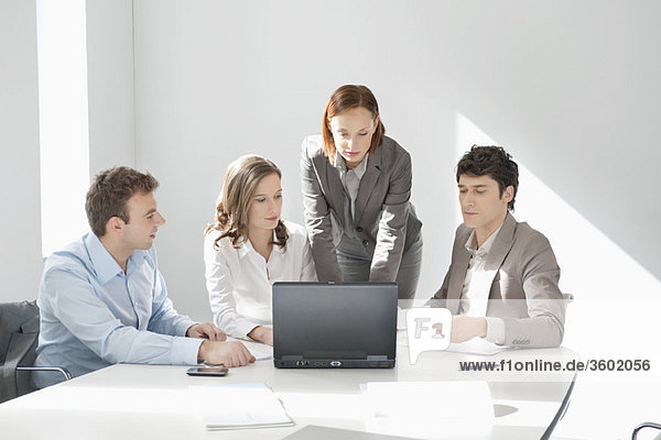 Business executives looking at a laptop in a board room