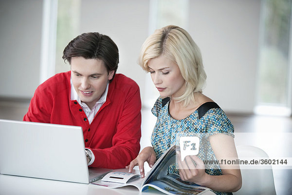 Man using a laptop with a woman reading a magazine