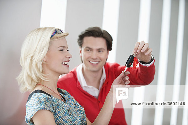 Man giving a car key to a woman