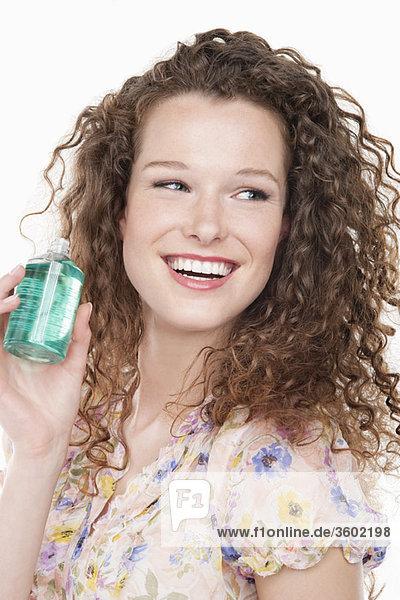 Nahaufnahme einer Frau  die eine Flasche Aromatherapieöl hält.