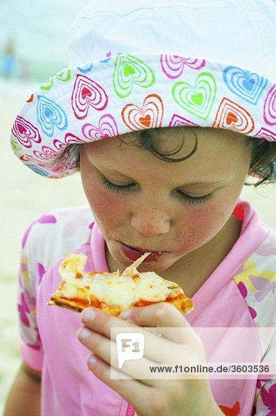 Kind isst Pizza am Strand