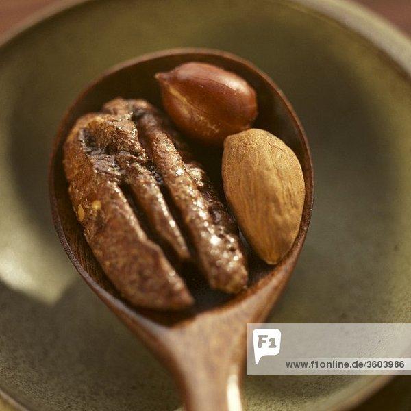 Salzpecannuss  -mandel und -erdnuss auf Holzlöffel