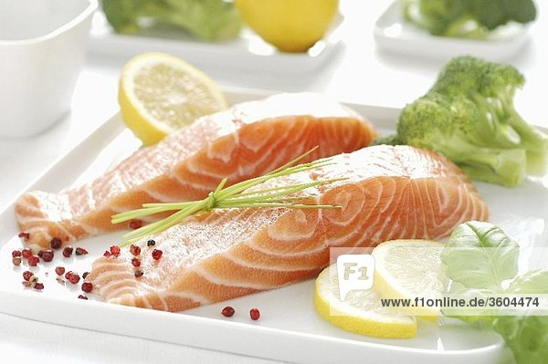 Raw salmon fillet  lemon slices  basil and broccoli