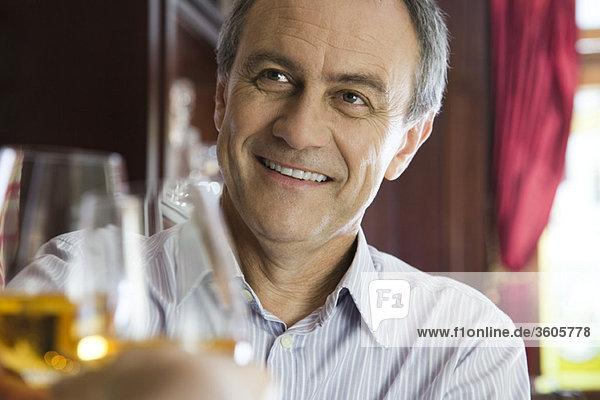 Erwachsener Mann klirrt mit Begleiter im Restaurant