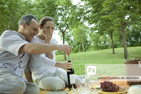 Erwachsenes Paar beim Picknick im Freien  Flasche Wein öffnen