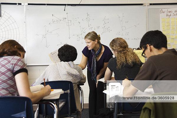 Teacher helping student in math class