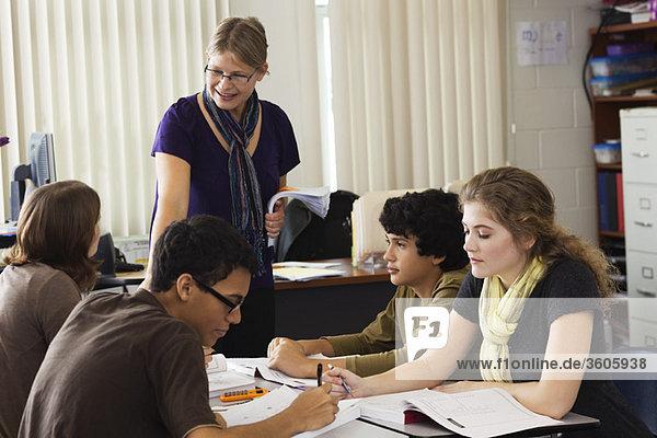 Lehrer hilft Gymnasiasten bei der Klassenarbeit