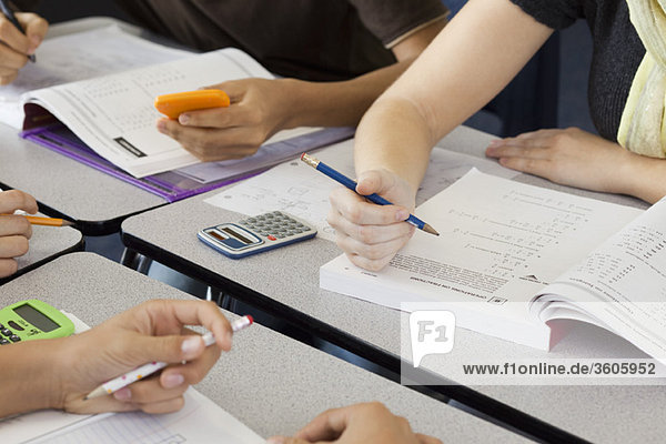 Students completing mathematics assignment together  cropped