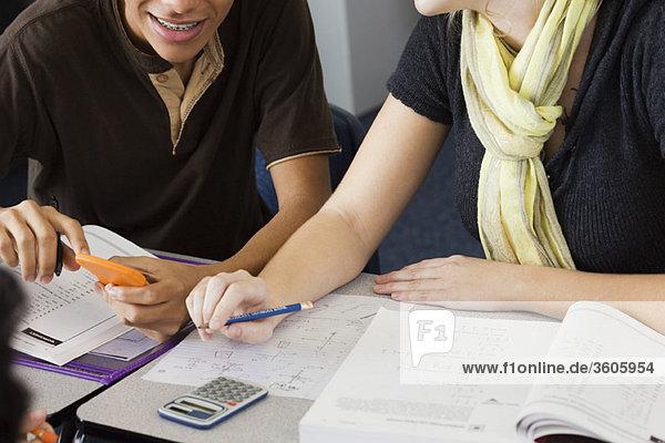 Mitschülerinnen und Mitschüler studieren gemeinsam Mathematik