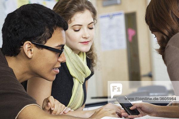 Teenager zeigt Handy an weibliche Freunde