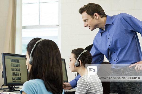 Lehrer assistiert Schülern im Computerlabor