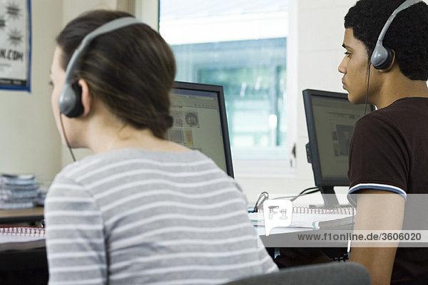 Gymnasiasten hören Kopfhörer im Computerlabor