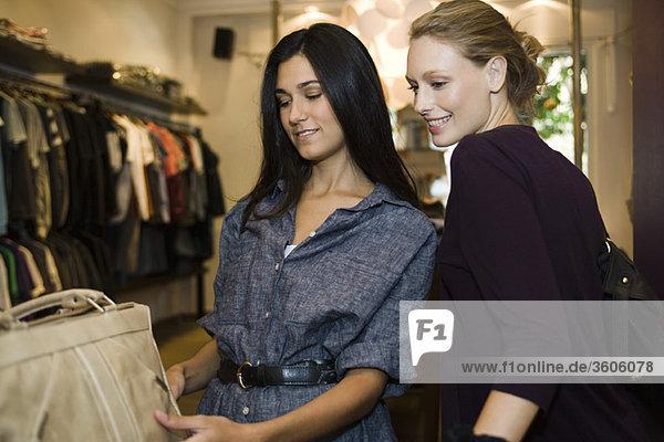 Freunde betrachten Handtasche in der Boutique