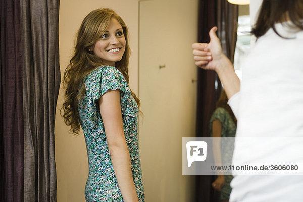 Frau  die ihrer Freundin das Daumen-hoch-Zeichen gibt  während sie sich im Umkleideraum anprobiert.