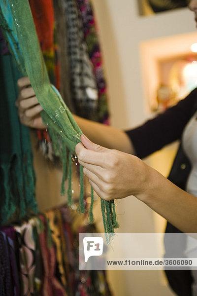Frau schaut auf den Schal im Laden  beschnitten