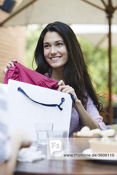 Frau sitzt im Café mit Freundin  zeigt Kleidung in der Einkaufstasche