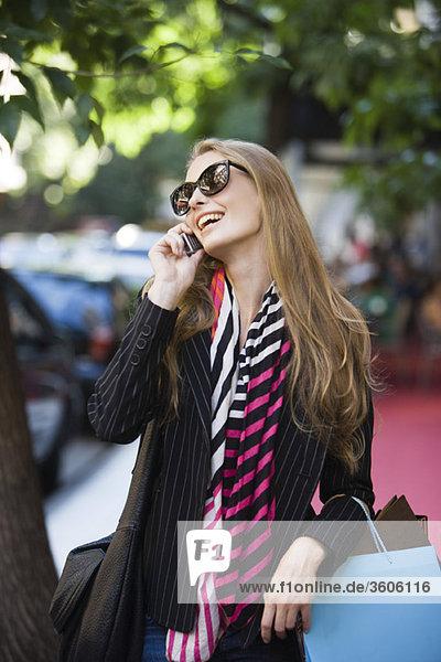 Shopper im Gespräch mit dem Handy beim Spaziergang im Freien