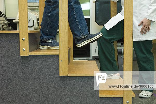 Patienten  die im Rahmen von Rehabilitationsübungen Schritte nach unten üben
