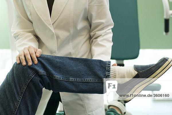 Arzt bei der Untersuchung der Bein- und Kniegelenkbeweglichkeit des Patienten