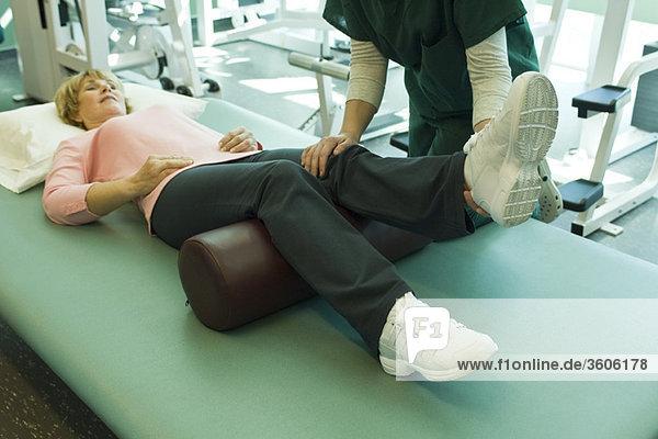 Frau wird von Physiotherapeutin behandelt