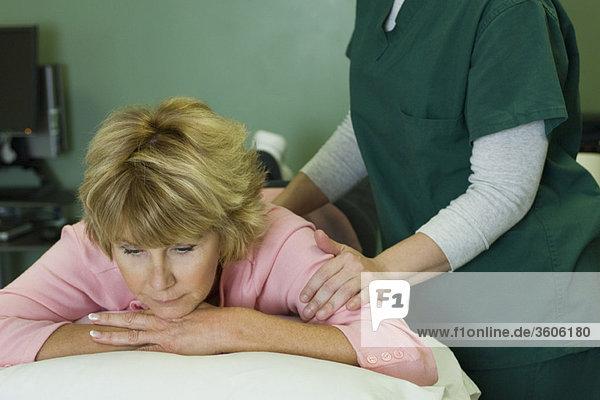 Frau genießt Massage durch Physiotherapeutin