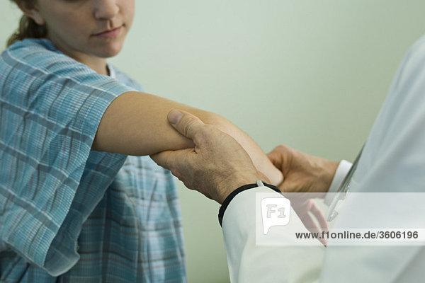 Arzt untersucht den Arm des Patienten