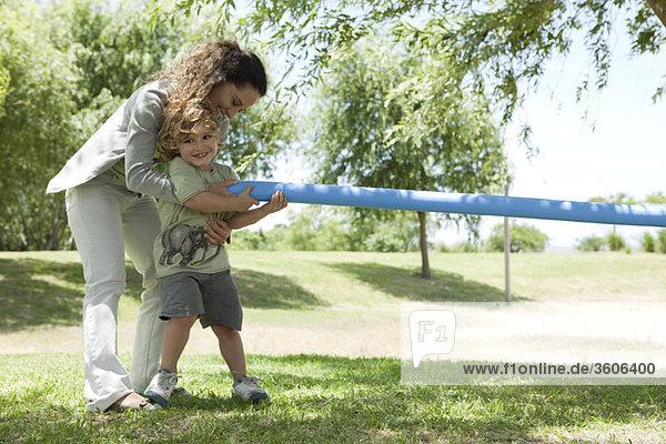 Mutter hilft dem jungen Sohn beim Tauziehen