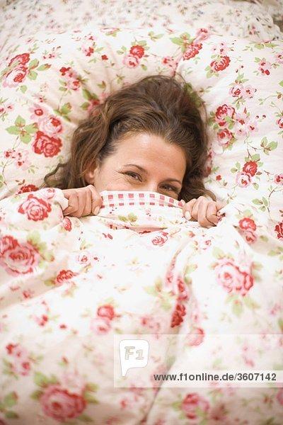 Frau versteckt sich im Bett