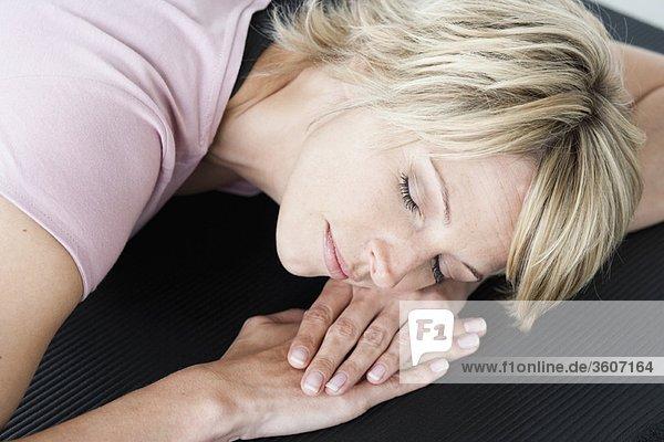 Frau entspannt auf Yogamatte
