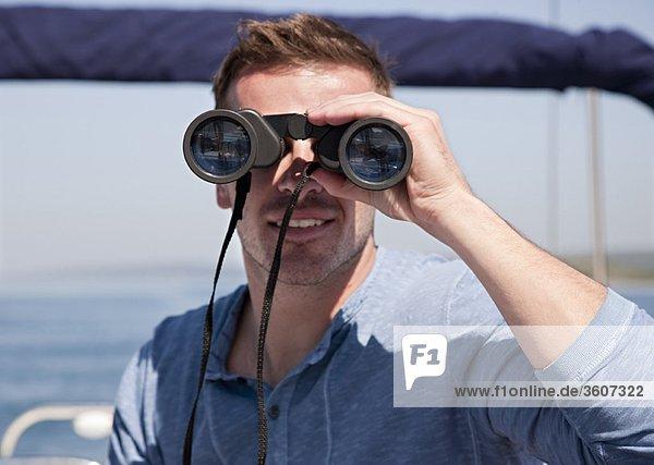Mann mit Fernglas auf der Yacht