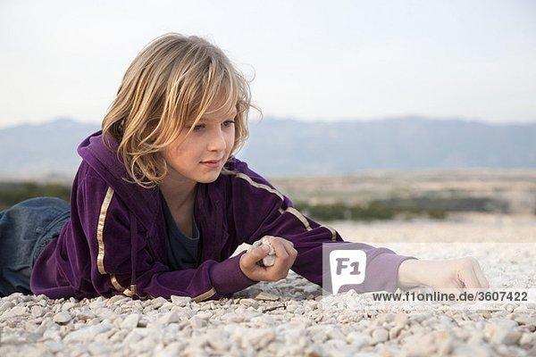 Mädchen sammelt Steine am Strand