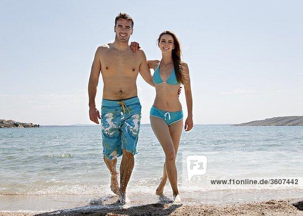Ein Paar  das am Strand aus dem Wasser kommt.