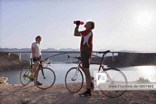 Radfahrer trinken Wasser auf dem Seeweg