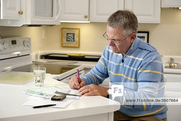Reifer Mann zahlt Rechnungen in der Küche