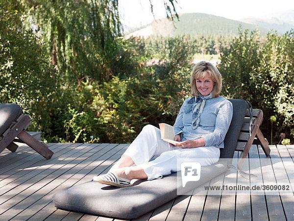 Frau Buch reifer Erwachsene reife Erwachsene Taschenbuch Liege Liegen Liegestuhl Sonne