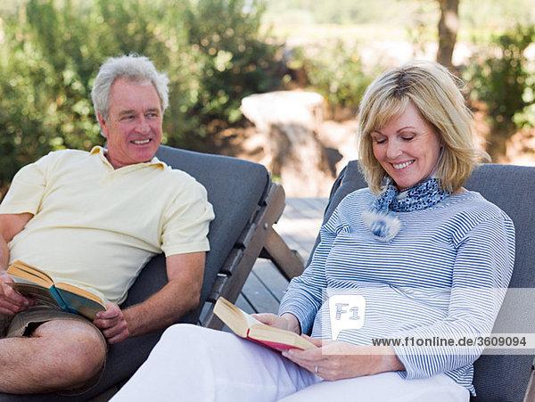 Erwachsene Paare lesen auf Liegestühlen im Garten