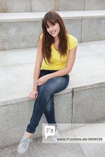 Junge Frau auf Stufe sitzend