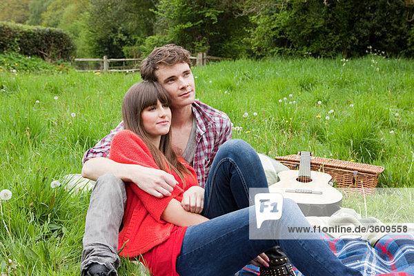 Junges Paar auf Decke im Feld