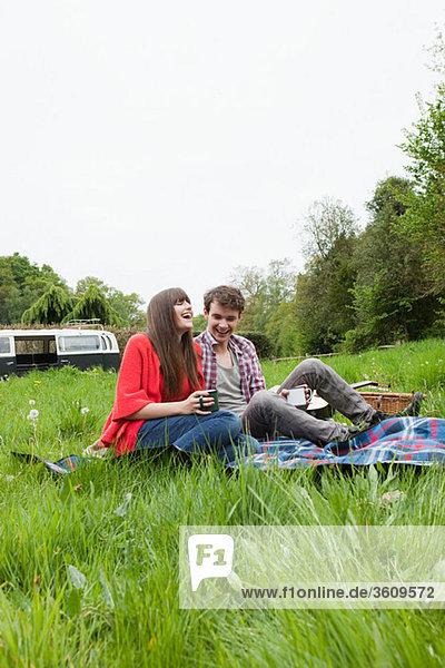 Junges Paar auf einer Decke in einem Feld