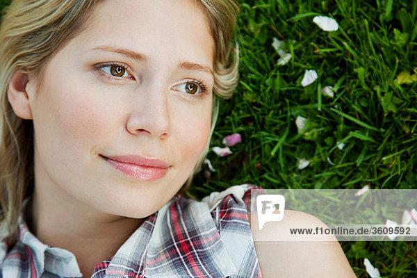 Gesicht der jungen Frau auf Gras liegend