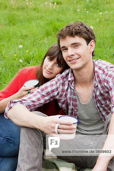 Young couple in field with cups