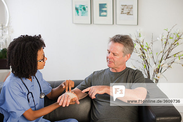 Nurse visiting man with wrist injury