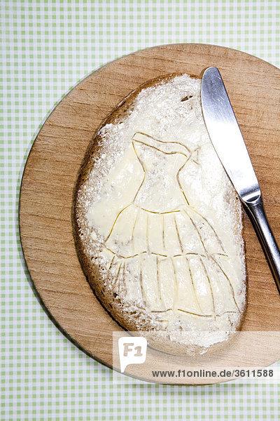 Scheibe Brot mit Frischkäse auf einem Brettchen