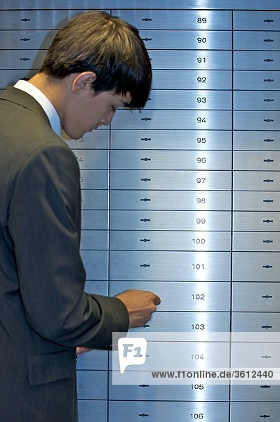 Mann öffnet ein Bankschließfach