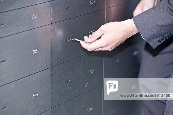 Mann öffnet ein Bankschließfach  close-up